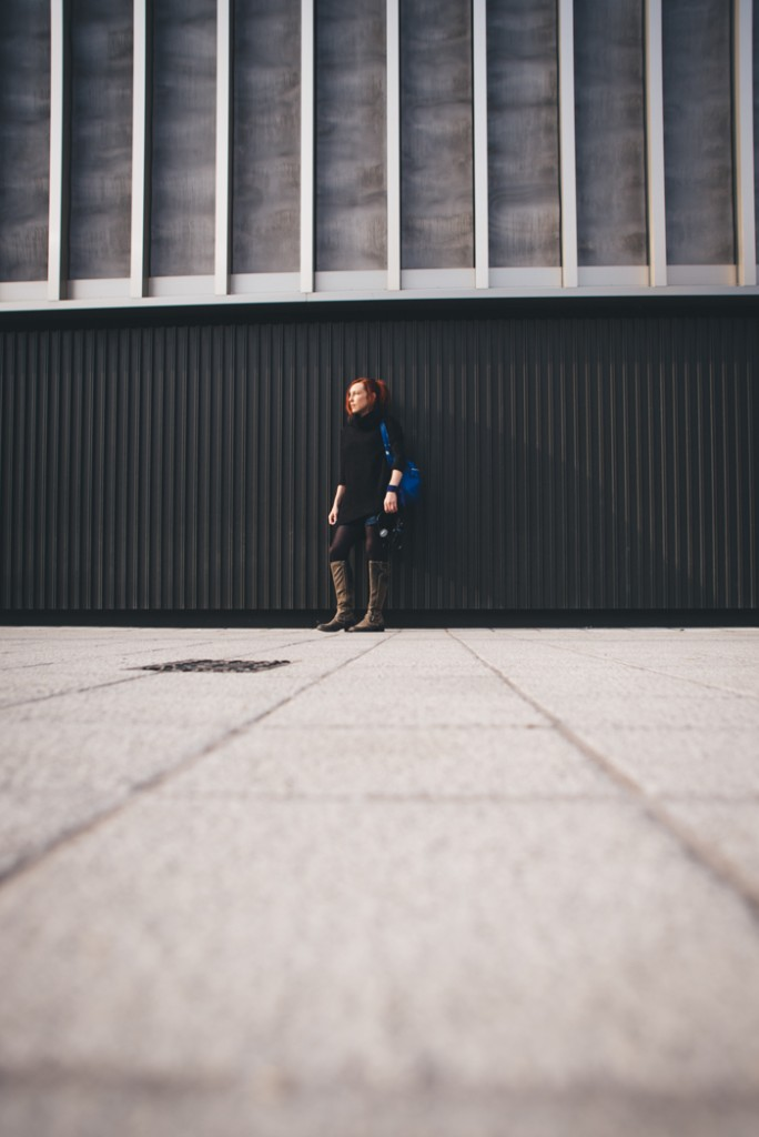 girl red hair blue bag against building low angle