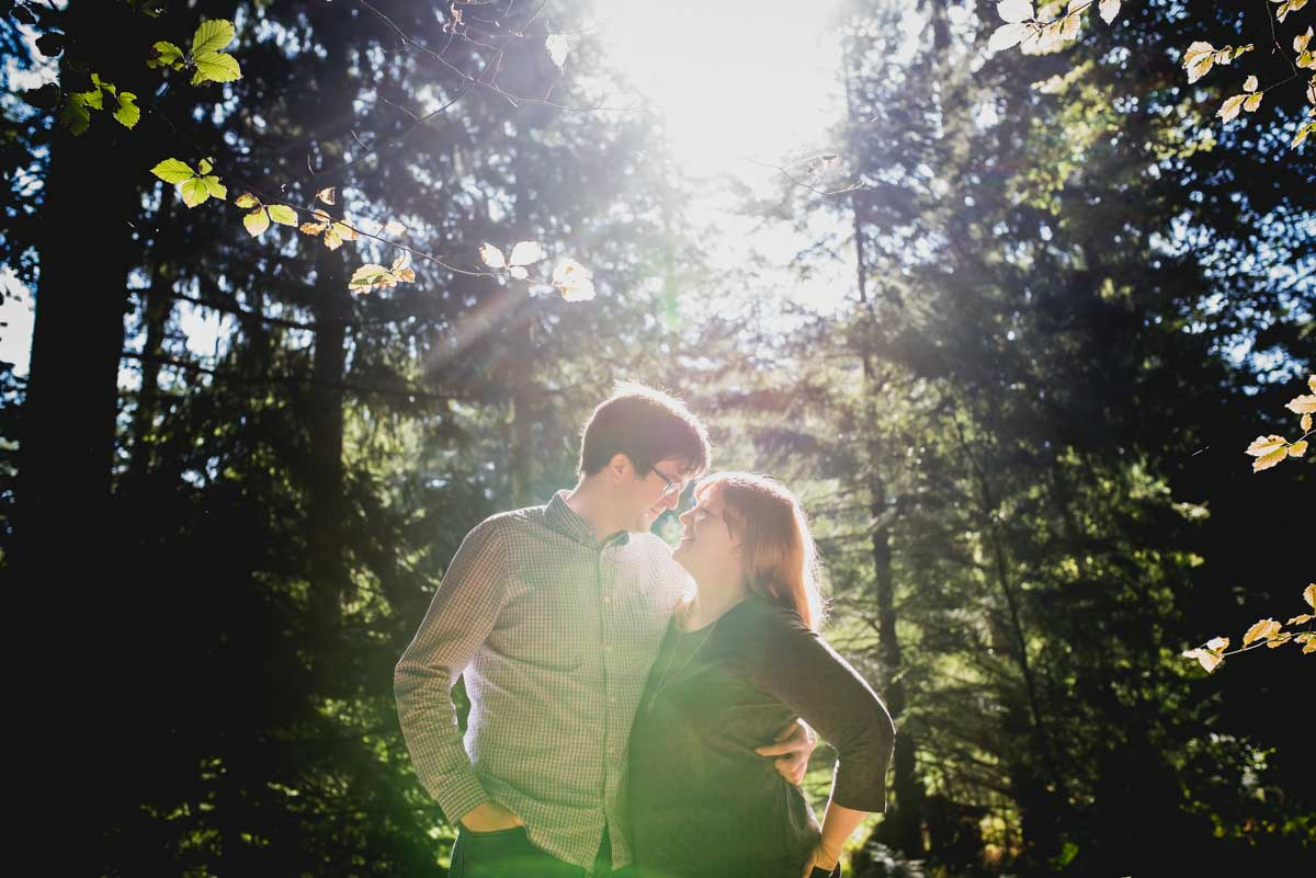 couple kissing in the forest with bright back lighting