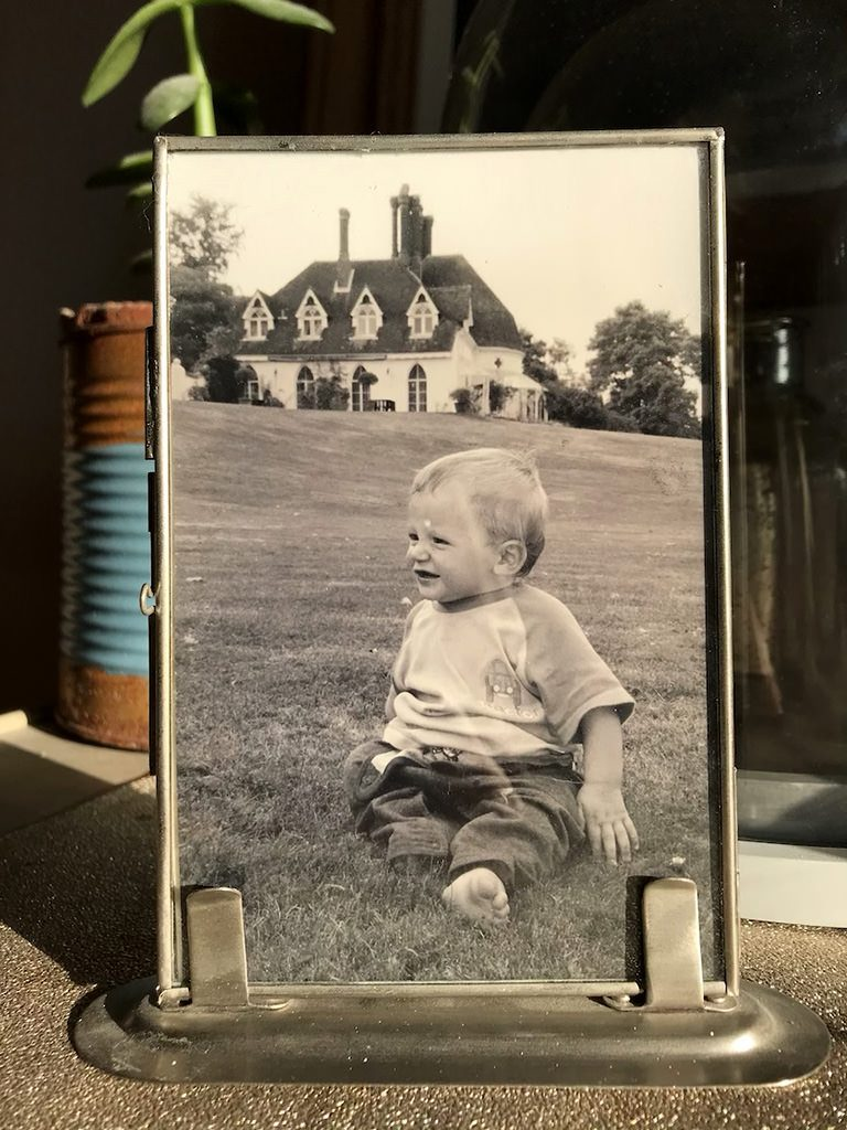 Little boy sat on the lawn at Houghton Lodge