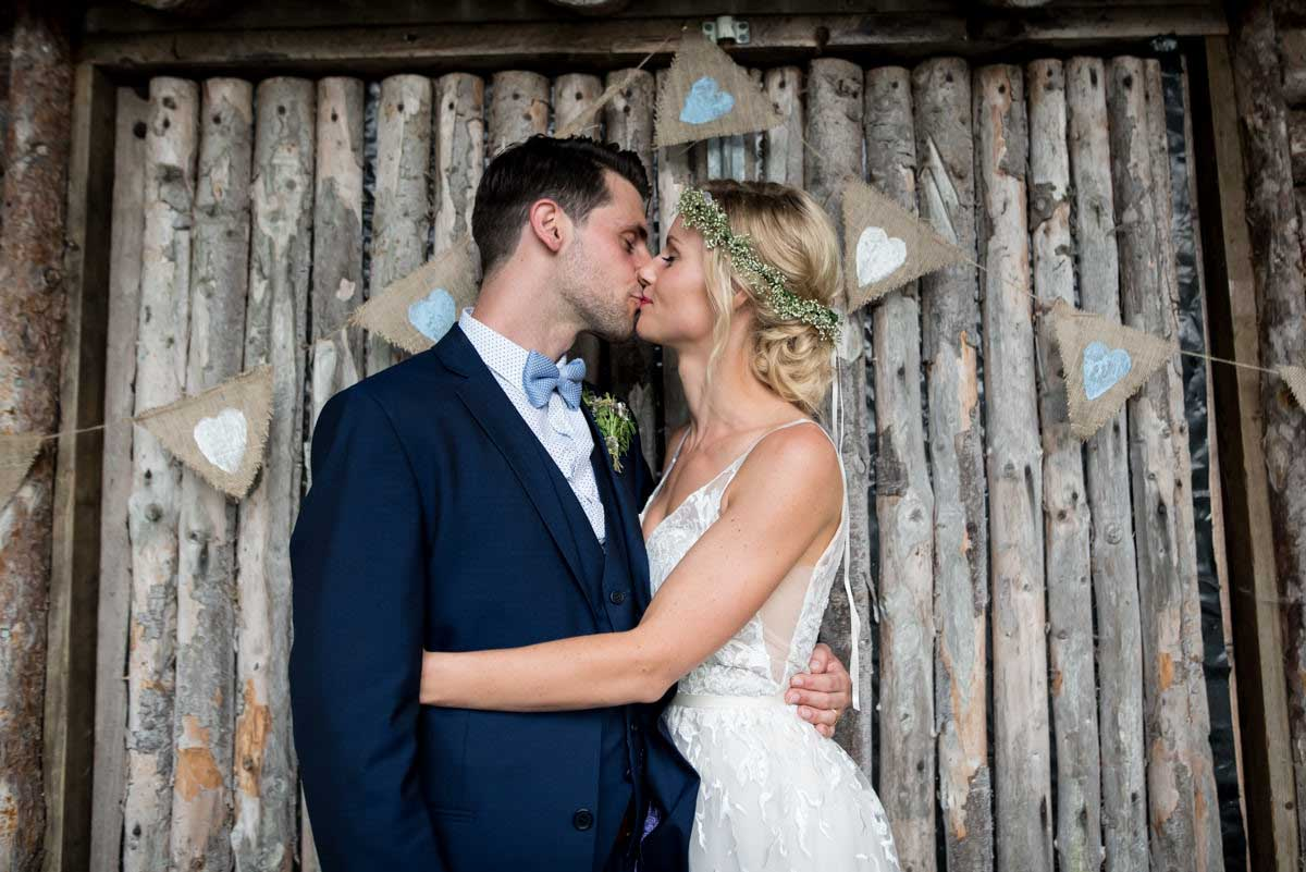 couple kissing in front of wooden lodge