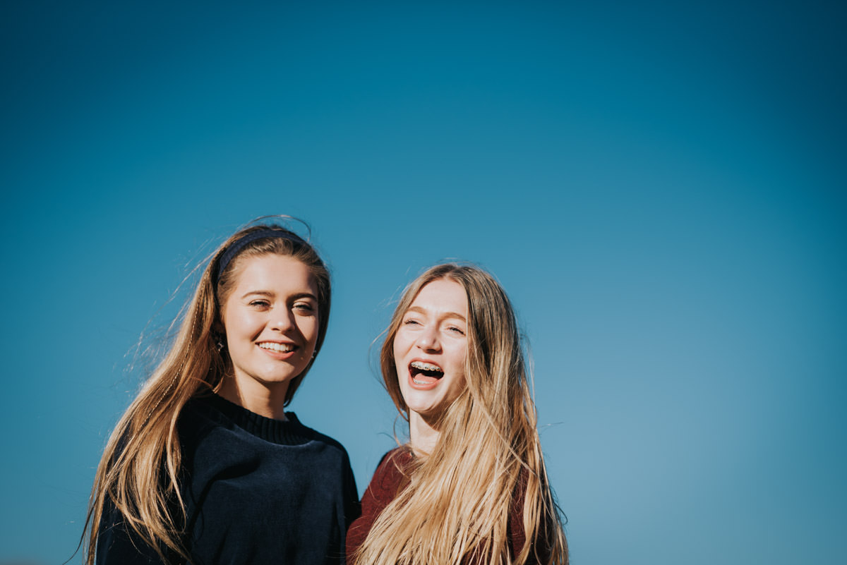 two sisters laughing against a blue sky