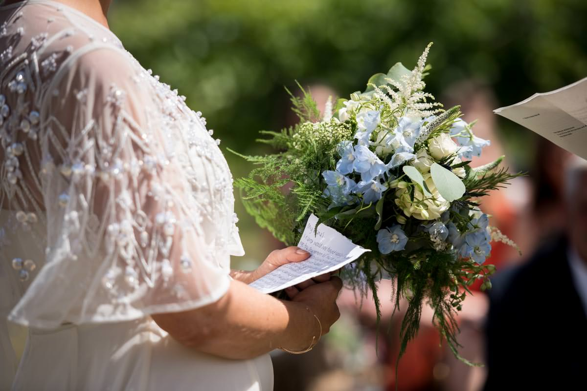 close up of brides vows and wedding flowers