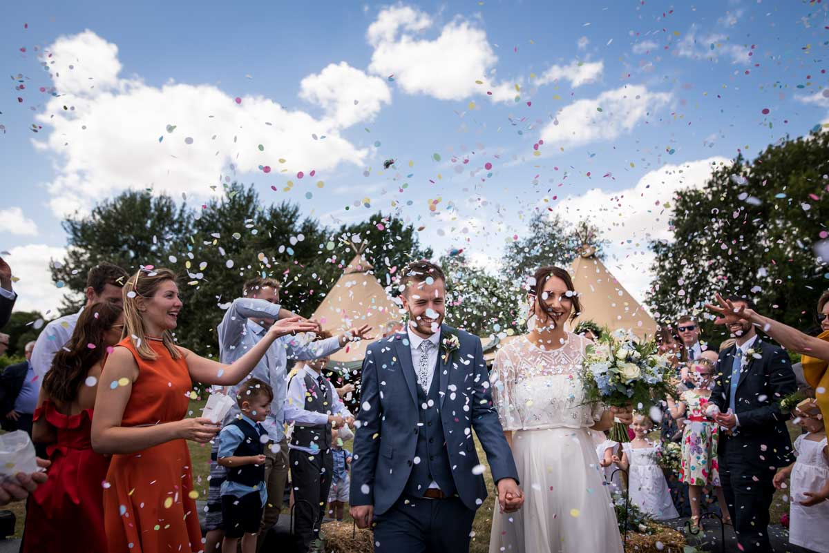 confetti over bride and groom in front of tipi