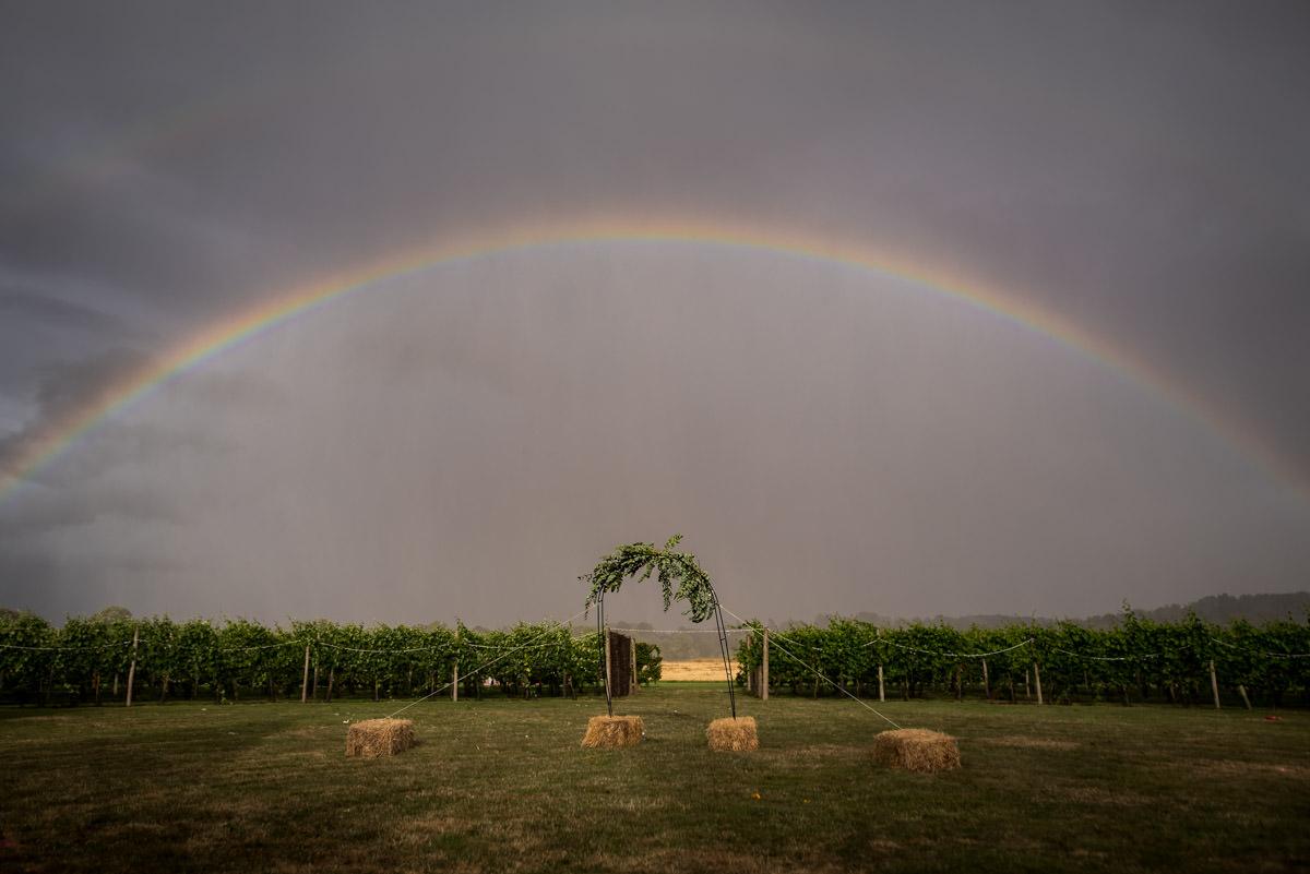 rainbow over outdoor wedding arch